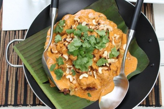 chicken tikka masala in a wok on top of banana leaves with a large spoon