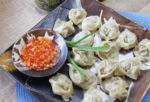 steamed Chinese shumai shrimp and turkey sausage dumplings on a plate with a side of sweet chili dipping sauce
