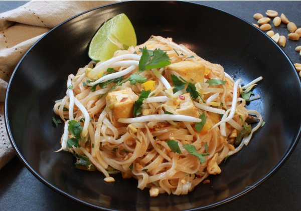 tofu pad Thai in a black bowl with a lime wedge garnish