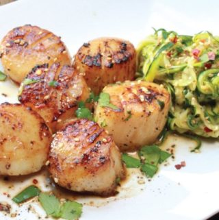 Pan-seared scallops on a white plate with a side of zucchini noodles