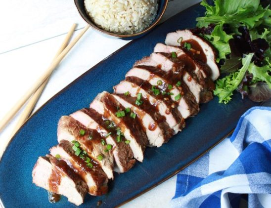 sliced pork tenderloin on a blue place with a side of brown rice and chopsticks