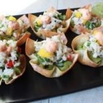 spicy crab salad on top of guacamole inside a baked wonton cup on a black plate