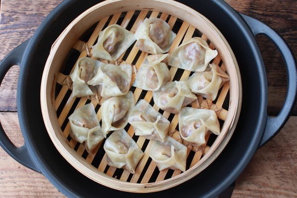 wontons in a steamer basket on top of a wok