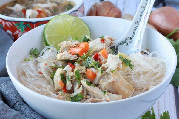 a white bowl of turkey noodle soup