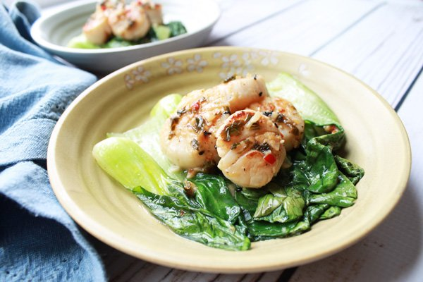 seared scallops on a plate over baby bok choy and chopsticks on the side
