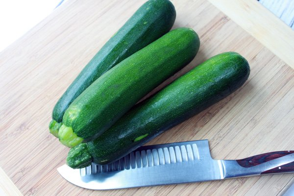 2 zucchinis on a wooden cutting board and a cutting knife