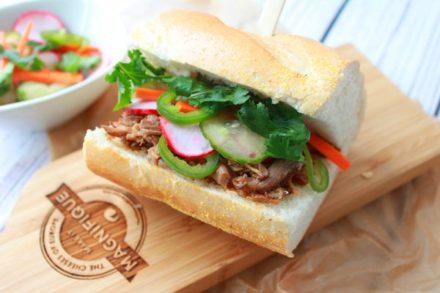 A pulled pork banh mi sandwich on a wooden board
