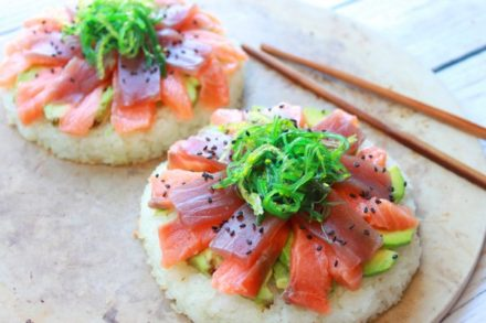 fresh tuna and salmon on top of avocado and round cakes of sushi rice