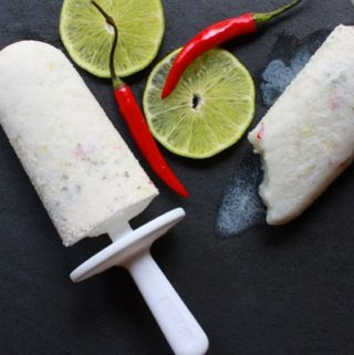 tropical coconut chili lime popsicles with lime slices and chili peppers