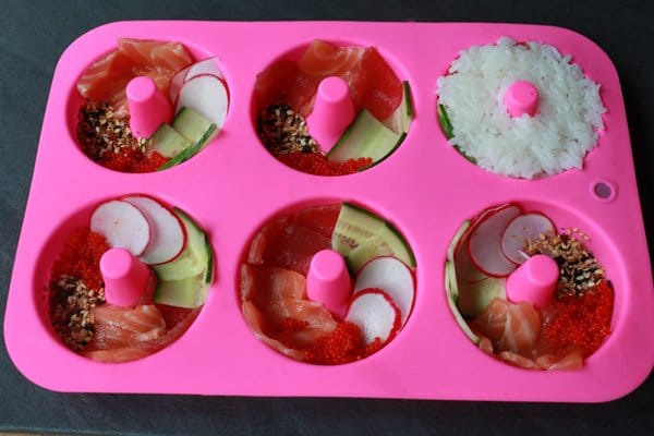 sushi donuts ingredients layered in a pink silicone donut mold