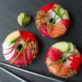 three sushi donuts on a gray board with silver chopsticks
