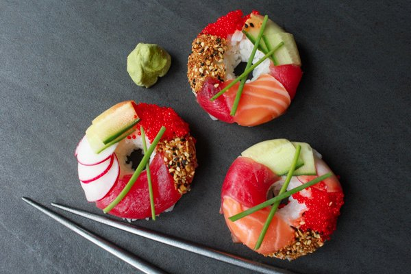 sushi donuts on a gray board with silver chopsticks