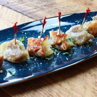 savory pumpkin wonton bites on a blue plate on top of a wooden board