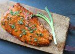 miso glazed salmon filet on a wooden board with a green onion along side