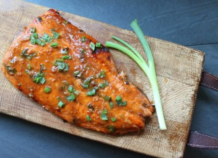 miso glazed salmon filet on a wooden board with a green onion along side