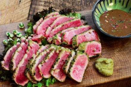 wasabi seared tuna sliced on a cutting board with a side of dipping sauce and wasabi