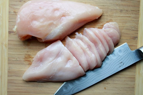 sliced chicken breasts on a wooden cutting board