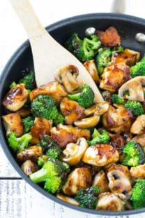 chicken and broccoli stir fry in a wok with a wooden spatula