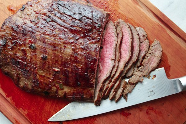 sliced grilled flank steak on a cutting board and a chefs knife