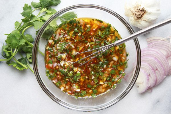 nuoc cham dipping sauce in a glass bowl with a whisk, shallots, garlic, and cilantro