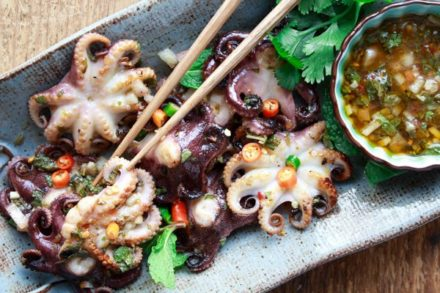 grilled baby octopus on a plate with nuoc cham dipping sauce on the side and chopsticks
