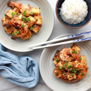 Two white bowls of General Tso's Shrimp and Tofu with chopsticks and a bowls of white rice on the side along with a blue napkin.