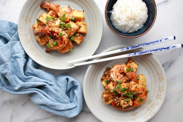 General Tso's shrimp and tofu in two white bowls with chopsticks and a bowl of white rice on the side.