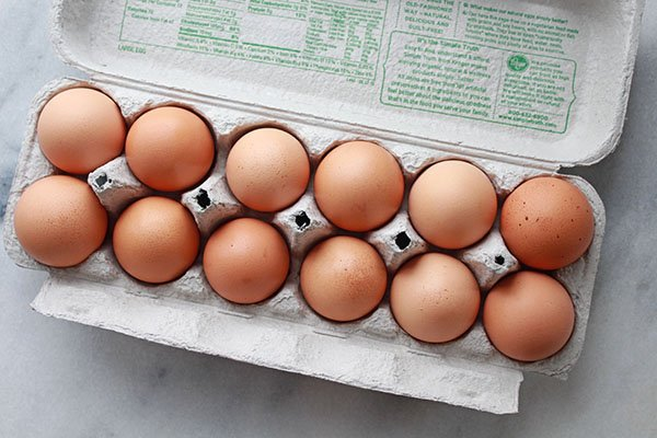 a dozen brown eggs in egg carton