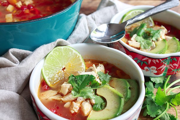 two bowls of chicken tortilla soup with a spoon