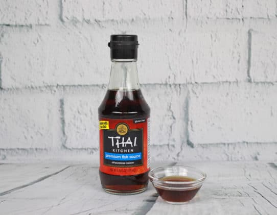 a jar of Thai fish sauce on a wooden board