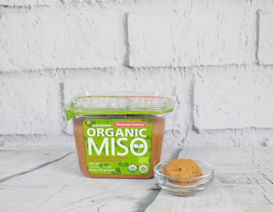 a container of organic miso paste on a white board with a tablespoon of paste in a glass bowl on the side