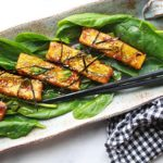 sesame seared tofu strips on a bed of spinach topped with sesame seeds and seaweed strips