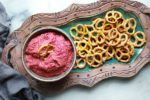 red beet hummus in a bowl with a side of pretzels for dipping