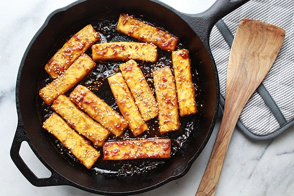sesame seared tofu strips coated with corn starch and sesame seeds searing in a cast iron pan