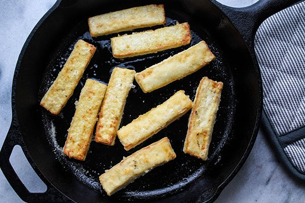 seared tofu strips in a cast iron pan