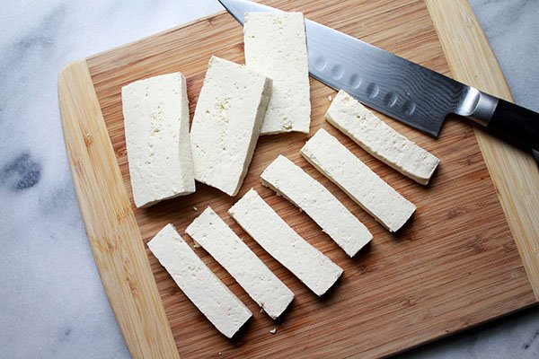 tofu strips on a cutting board with a chefs knife on the side