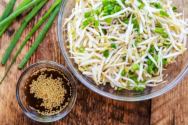 bean sprouts in a bowl with green onions and dressing on the side