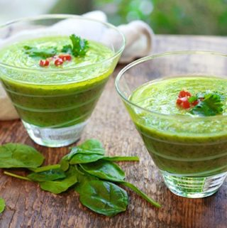 green gazpacho soup in clear class bowls with fresh spinach