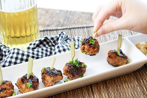sweet and spicy BBQ meatballs on a white platter with a beer in the background