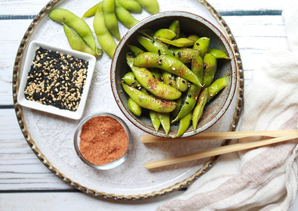 a bowl of spicy edamame on a white plate with sesame seeds and sriracha seasoning