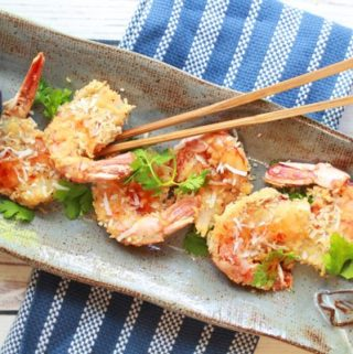 Baked coconut shrimp on a gray serving platter with wooden chopsticks on top and a small bowl of chili sauce on the side.