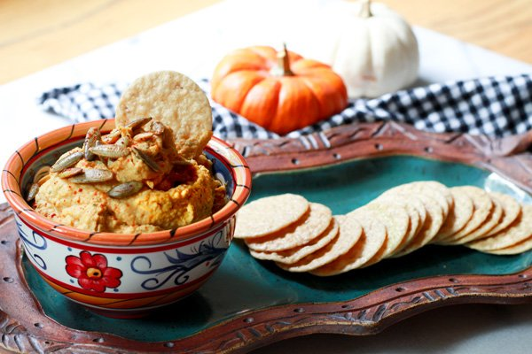 pumpkin hummus in a bowl with rice crackers on the side