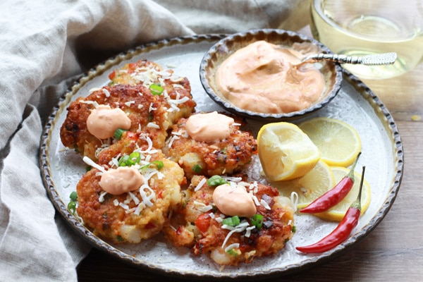 golden brown gluten-free coconut shrimp cakes with a spicy aioli sauce