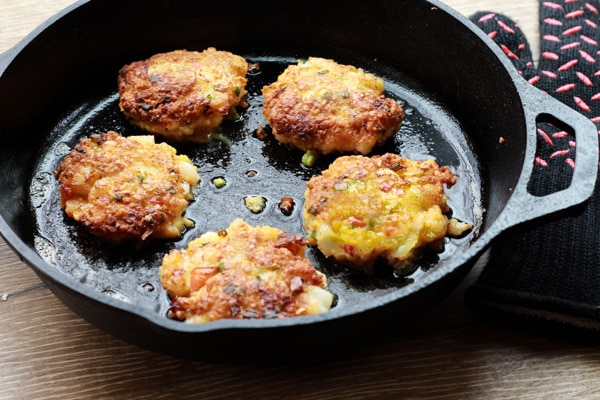 golden brown gluten-free coconut shrimp cakes frying in a skillet