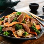 stir-fry beef and broccoli on a black plate with chopsticks