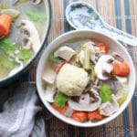 matzo ball soup in a bowl with veggies and a soup spoon