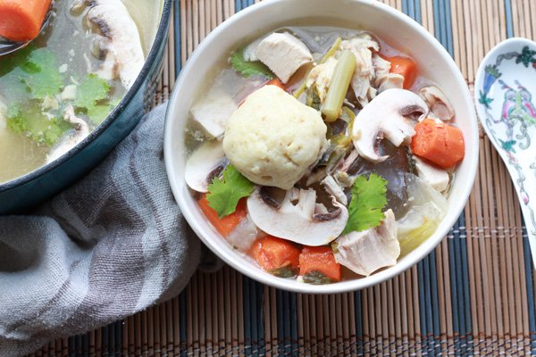 matzo ball soup in a bowl with veggies