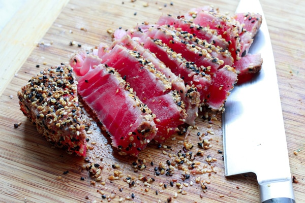 sliced sesame seared tuna on a cutting board with a chef's knife