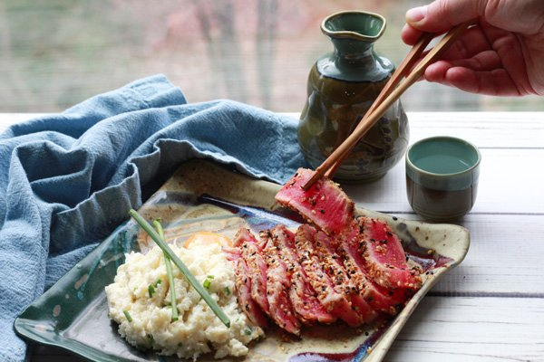 sesame seared tuna with cauliflower mash on a plate with chopsticks