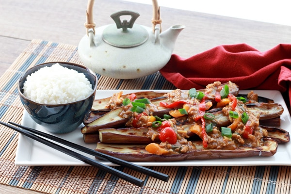 Chinese eggplant on plate topped with garlic sauce on a plate with chopsticks and a side of white rice